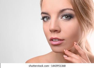 Portrait of beautiful young woman with eyelash extensions on light background