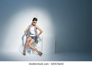 portrait of beautiful young woman in fancy dress sitting on chair in light background
