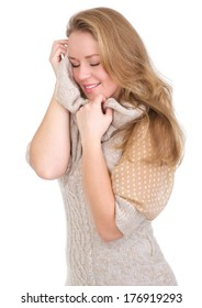 Portrait of a beautiful young woman feeling soft sweater against face