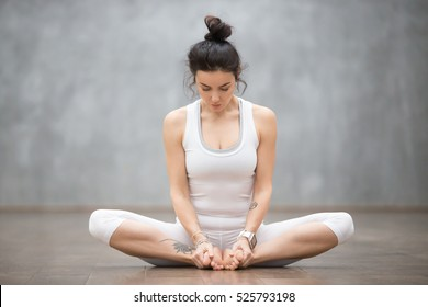 Portrait of beautiful young woman with floral tattoos working out against grey wall, doing yoga or pilates exercise, sitting in baddha konasana, bound angle, cobbler, butterfly pose. Full length shot