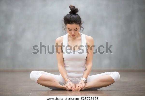 美麗的年輕女子與花卉紋身在灰牆上工作的肖像,做瑜伽或普拉提運動,坐在 baddha konasana,綁定角度,鞋匠,蝴蝶姿勢。 全長射門