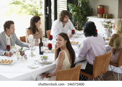 Portrait of beautiful young woman with friends having a dinner party at home
