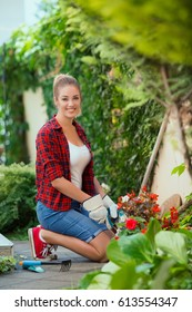 Portrait of beautiful young woman gardening in front or back yard