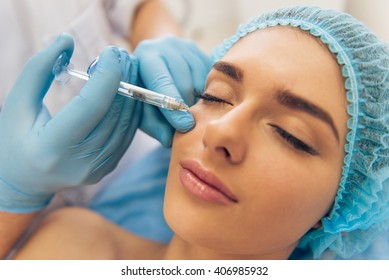 Portrait of beautiful young woman getting an injection in face, lying with closed eyes, close-up
