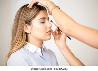 Portrait of a beautiful young woman getting her make-up done in a beauty salon
