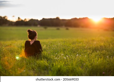 Portrait of a beautiful young woman or girl on very green meadow watching the sunset enjoying nature summer evening outdoors. Sunshine. Copy space.