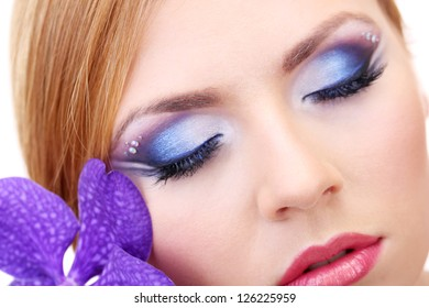 Portrait of beautiful young woman with glamour make up and flower, close up