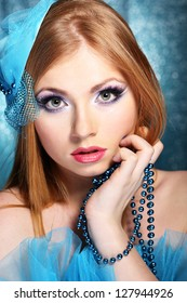 Portrait of beautiful young woman with glamour make up, on blue background