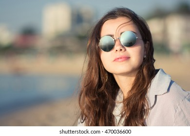 portrait of a beautiful young woman with glasses in the background of the sea