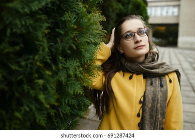 Portrait of a beautiful young woman in glasses, on a green background of spring nature.