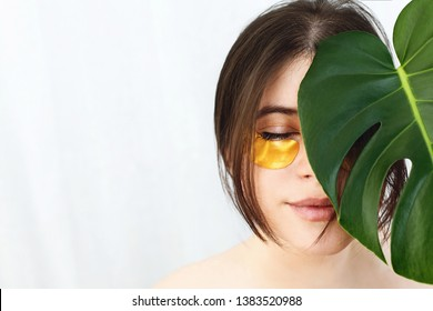 Portrait of beautiful young woman with golden eye patches at green monstera leaf on white background, copy space. Natural skin care. Lifting anti-wrinkle collagen patches under eyes. Eye Skin Care