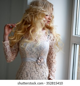 Portrait of beautiful young woman with golden hair in luxury dress in interior. Fashion beauty portrait