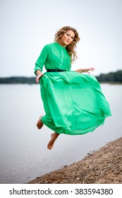 Portrait of beautiful young woman in green dress on water background.