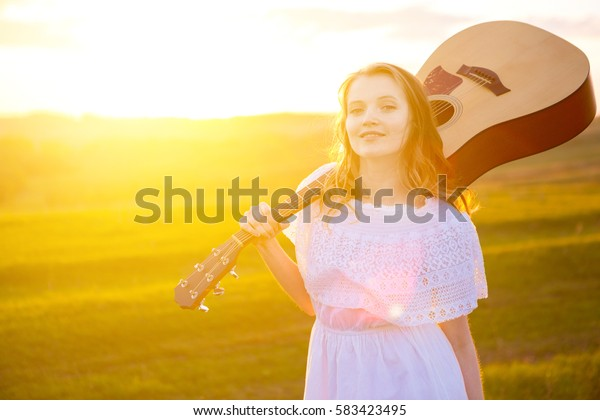 portrait of the beautiful young woman with guitar in the field