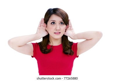 Portrait of a beautiful young woman with hands behind her ears against white background.