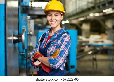 Portrait of beautiful young woman in hardhat smiling confidently at camera enjoying work in modern factory