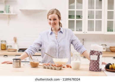 Portrait of beautiful young woman having breakfast in the kitchen