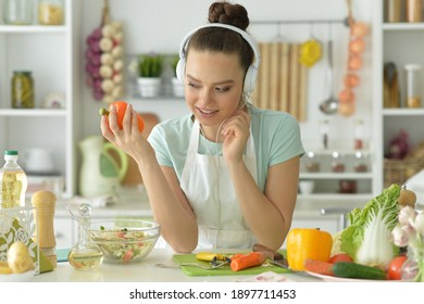 Portrait of beautiful young woman in headphones making salad at home