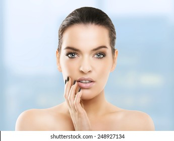 Portrait of beautiful young woman with healthy skin at Spa, blue background