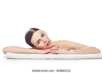 Portrait of beautiful young woman with healthy clean skin rest on a towel isolated on white background