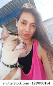 Portrait of beautiful young woman with her dog using mobile phone