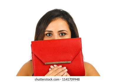 Portrait of a beautiful young woman hiding behind a red handbag against a white background