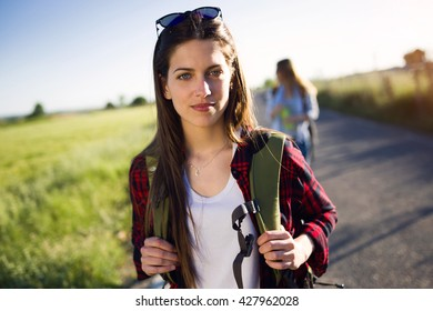 Portrait of beautiful young woman hiker walking on the road.