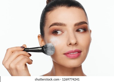 Portrait of a beautiful young woman holding a brush in her hand and applying powder to her face with a brush. White background