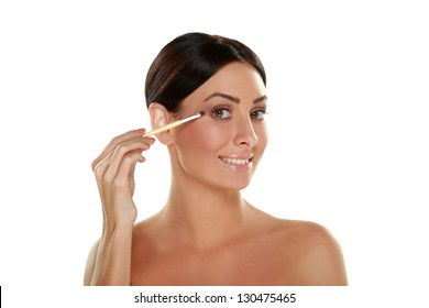 Portrait of beautiful young woman holding brush and applying make up