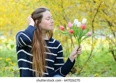The portrait of beautiful young woman holding color tulips in the park.