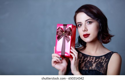 portrait of beautiful young woman holding gift on the wonderful grey studio background