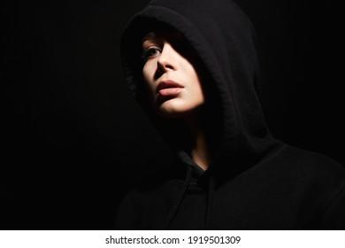 portrait of beautiful young woman in Hood. hipster girl in dark weared Hoodie