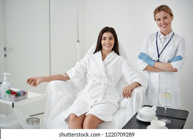 Portrait of beautiful young woman with intravenous drip sitting on armchair while physician standing beside her. They looking at camera and smiling