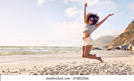 Portrait of beautiful young woman jumping in air at the beach. African female enjoying a summer day at the sea shore.