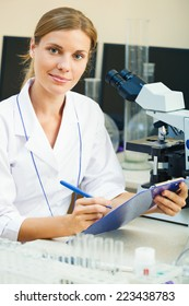 Portrait of beautiful young woman in a laboratory sitting on her workplace looking at camera