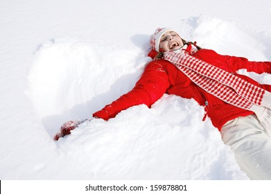 Portrait of a beautiful young woman laying down on a frozen snow lake moving her arms and legs up and down creating a snow angel figure, playing games during a sunny winter  vacation.