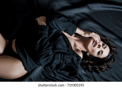 Portrait of a beautiful young woman laying on a satin bed