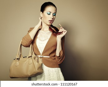 Portrait of beautiful young woman with a leather bag. Fashion photo