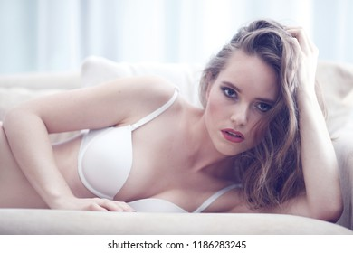 Portrait of beautiful young woman in lingerie on couch