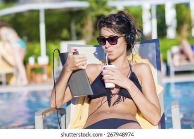Portrait of beautiful young woman listening music and drinking juice on the pool