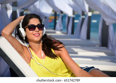 Portrait of beautiful young woman listening music with headphones  on the beach