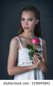 A portrait of a beautiful young woman with long brown hair, holding a pink rose, wearing white dress
