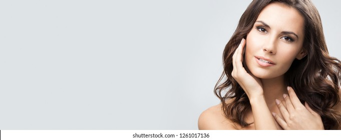 Portrait of beautiful young woman with long curly hair, with empty copyspace area for slogan, advertising or text message, over grey background.