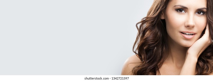 Portrait of beautiful young woman with long hair, against grey background, empty copy space place for some text, advertising or slogan