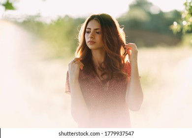 Portrait of beautiful young woman in with long brown hair in red pattern dress posing outdoors at summer sunset, dreaming, sensual, blurry white smoky background