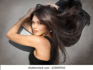 Portrait of beautiful young woman with long hair on gray background