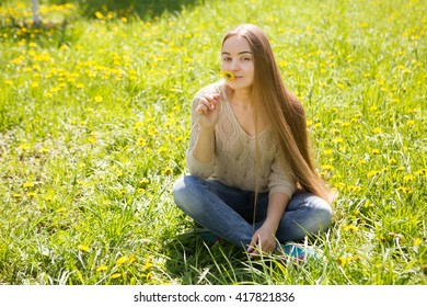 the portrait of the beautiful young woman with long hair with a flower sits on a grass in park