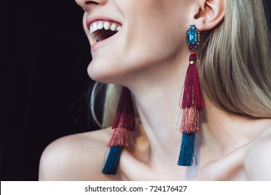 Portrait of a beautiful young woman with long blonde hair, chic makeup and big smile, wears a big gorgeous colorful earrings with a brooch.