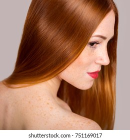 Portrait of a beautiful young woman with long red hair. Close-up photo in profile