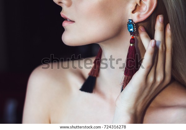 Portrait of a beautiful young woman with long blonde hair and chic makeup, wears a big gorgeous colorful earrings with a brooch.